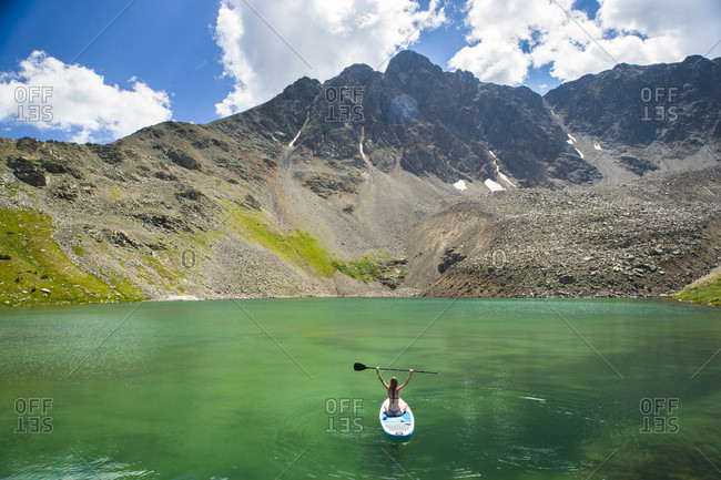 Aerial view of young female sitting on paddle board on high alpine lake in Colorado, USA