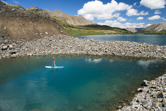 Aerial view of young female standing on paddle board on high alpine lake in Colorado, USA