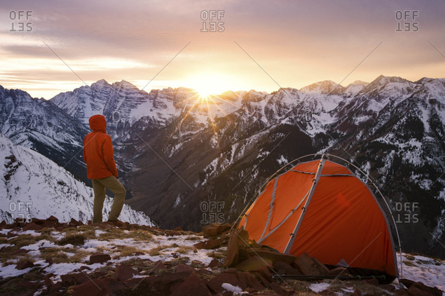 Backpacker next to tent at sunset in Maroon Bells Snowmass Wilderness in Aspen, Colorado, USA