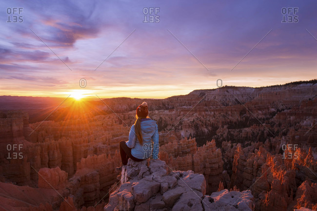 Woman looking at view of Bryce Canyon National Park at sunrise, Utah, USA