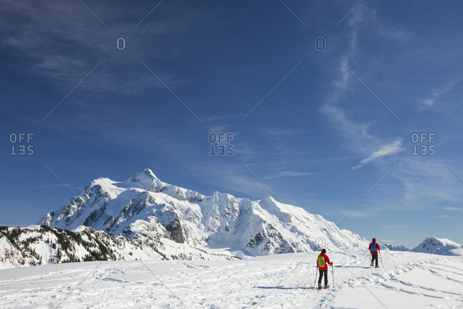 Two people snowshoeing below Mount Shuksan in winter, North Cascades National Park, Washington State, USA