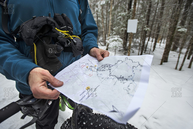 Man reading map during winter fat-tire biking, Littleton, New Hampshire, USA
