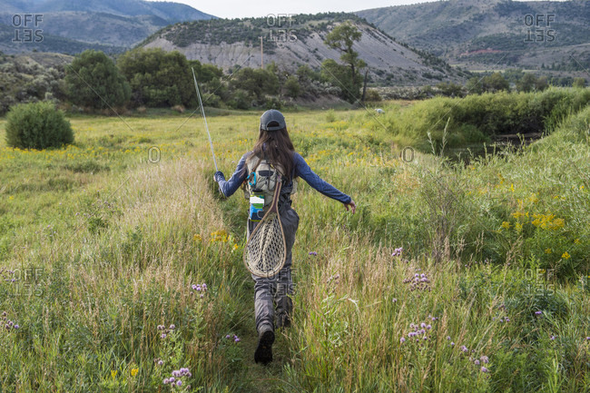 Female angler walking through meadow, Colorado, USA