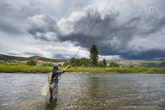 Clouds over women fishing in river, Colorado, USA