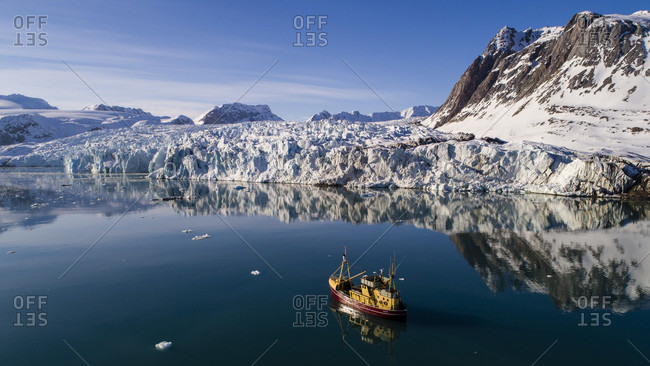 Fishing boat in Arctic scenery with glacier and snowy mountains, Kongsfjorden, Spitsbergen, Norway