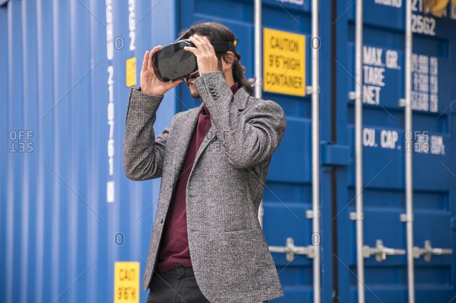 Man in blazer using VR goggles