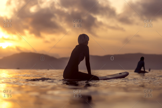 Female surfer in sea at sunset