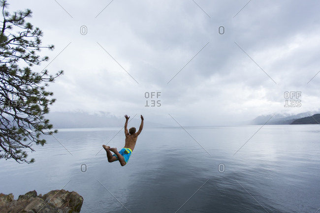 Adult man jumping off a cliff into a lake with his arms spread above his head