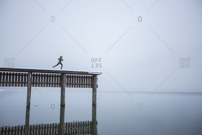 Humorous image of a woman appearing to run off the end of a tall dock into a lake far below