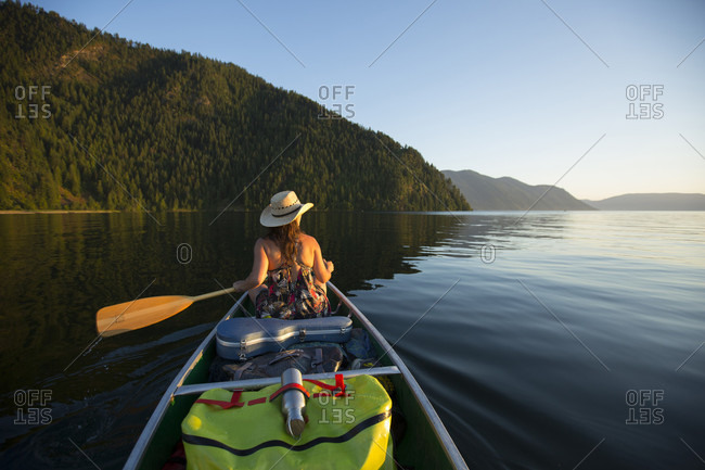 Adult woman canoeing down a river with all of her gear for overnight camping