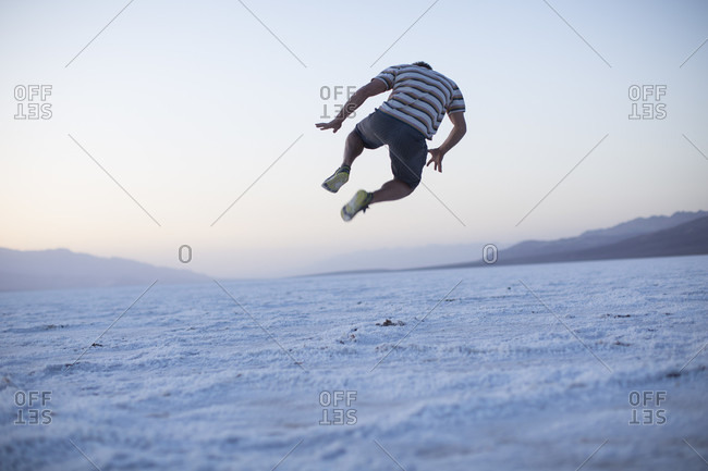 Adult man leaping of the salt pan in a wide open desert area