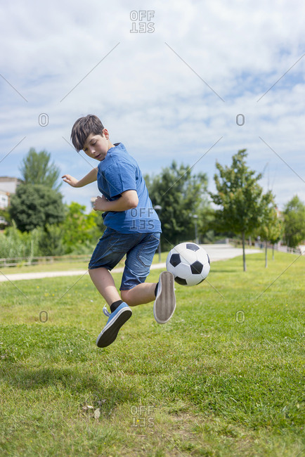 Teenager plays soccer at the park