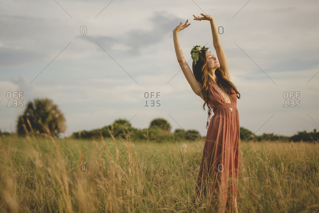 A woman in a brown dress with floral crown in a field reaching up towards the sky as she takes a deep breath in