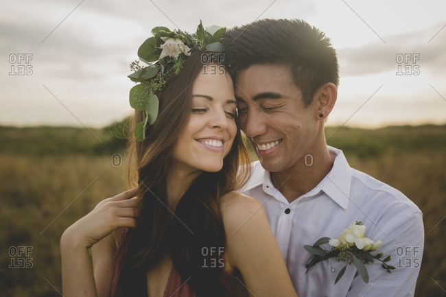 A couple in a field snuggle in with each other forehead to forehead and laugh