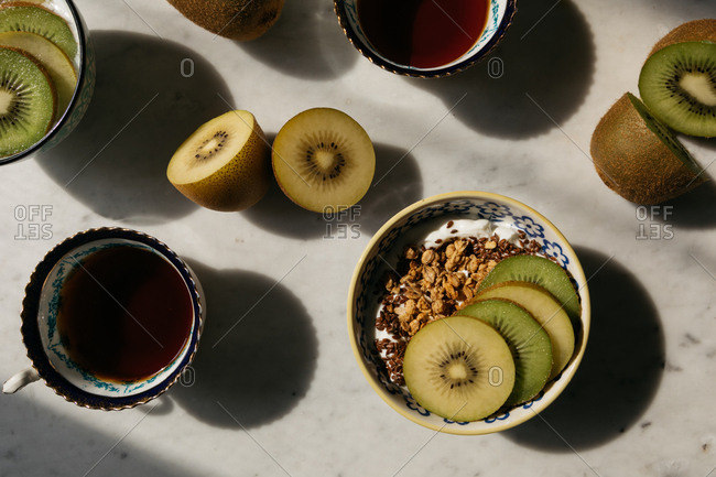 Overhead view of breakfast of slices of Kiwi fruit laid on muesli and black tea
