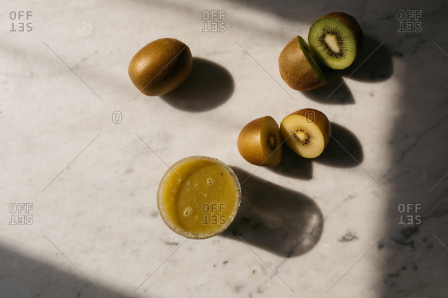 Top down view of kiwi fruits cut into halves and a glass of kiwi fruit juice
