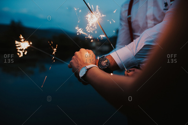 Couple holding hands and sparklers