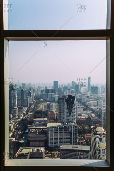 Bangkok, Thailand - March 11, 2016: Skyscrapers in city against sky seen through window