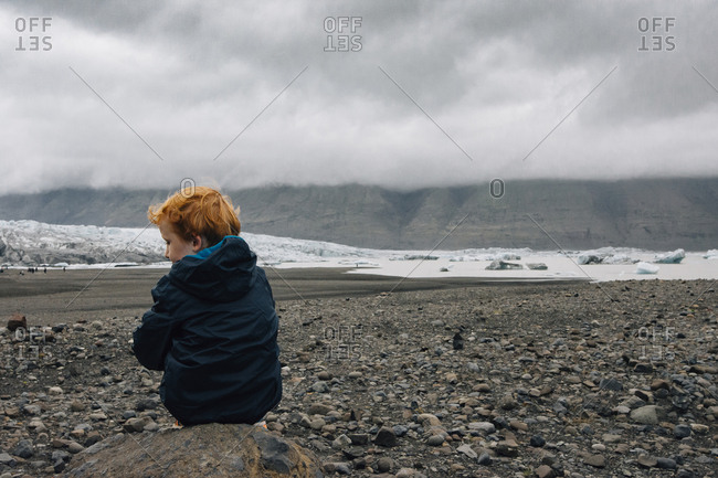 Rear view of boy sitting on rock against cloudy sky during winter
