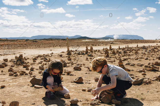 Siblings playing with rocks at desert during sunny day