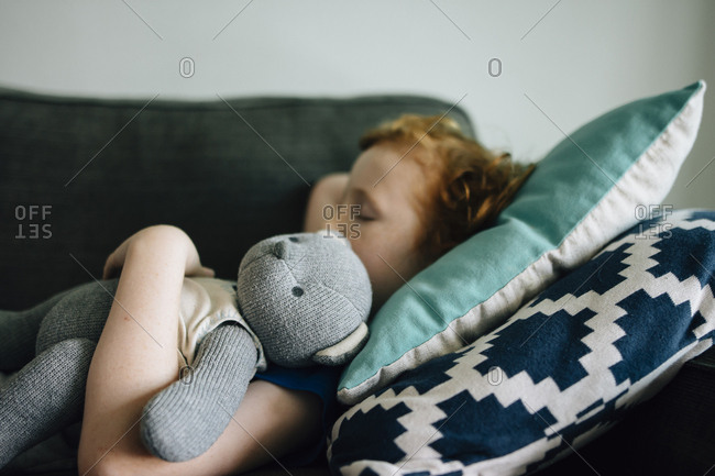 Side view of boy sleeping with teddy bear on couch at home