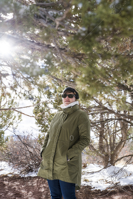 Woman with hands in winter coat's pockets standing by branches at desert during winter