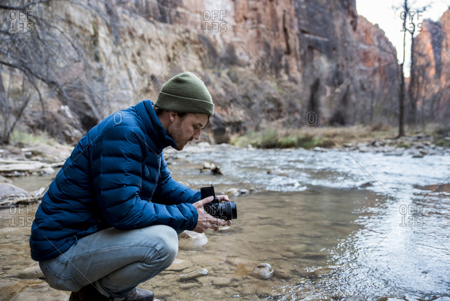 Side view of man with camera crouching by stream against rock formations