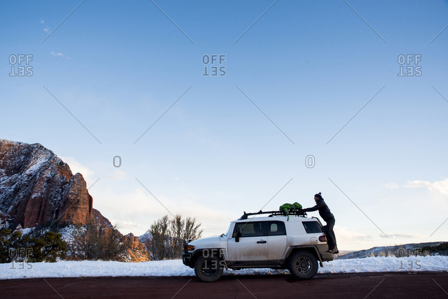 Side view of man putting backpack on off-road vehicle at desert against sky during winter