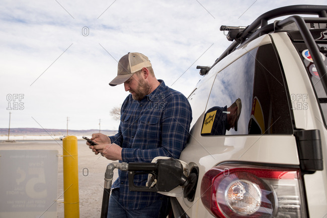 Mid adult man using smart phone while standing by car at gas station