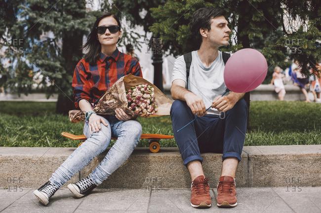 Girlfriend wearing sunglasses holding bouquet while sitting on skateboard by boyfriend in city