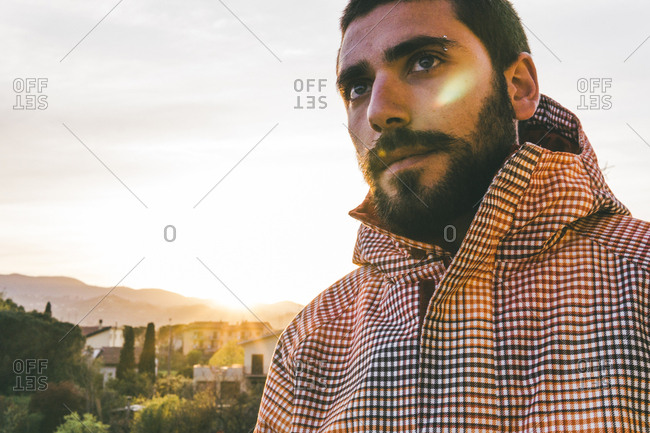 Thoughtful young man wearing hooded shirt while looking away against sky during sunset