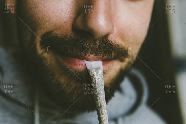 Midsection of bearded man carrying marijuana joint in mouth