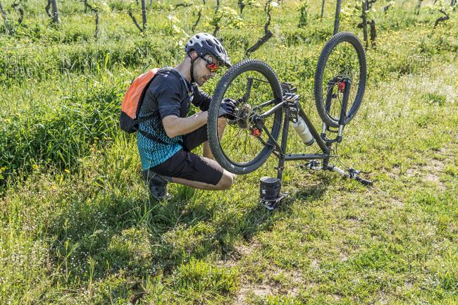 Full length of young man repairing mountain bike on field
