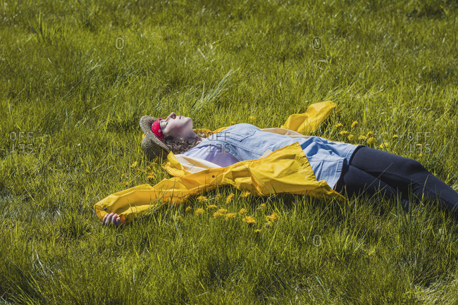 Carefree young woman lying on grassy field at park