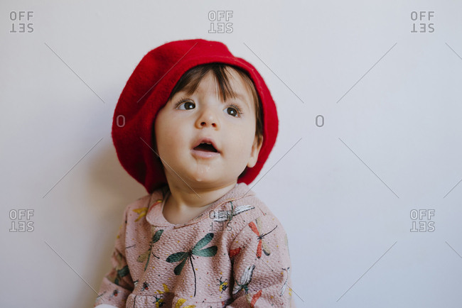 Cute baby girl drooling while looking up against wall at home
