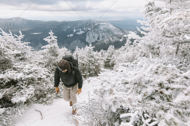 Hiker with backpack walking in forest during winter