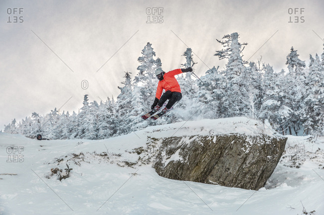 Full length of man doing stunt while skiing on snow against trees during winter