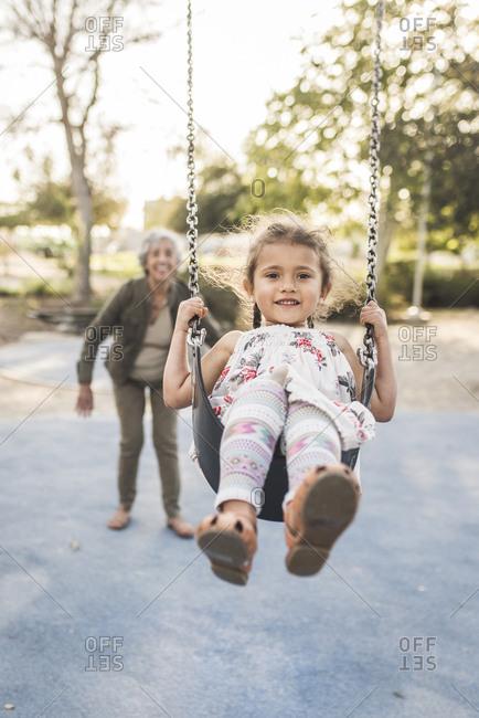 Happy grandmother pushing granddaughter swinging at playground