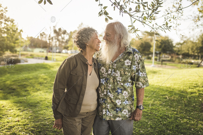 Loving senior couple looking each other face to face while standing at park