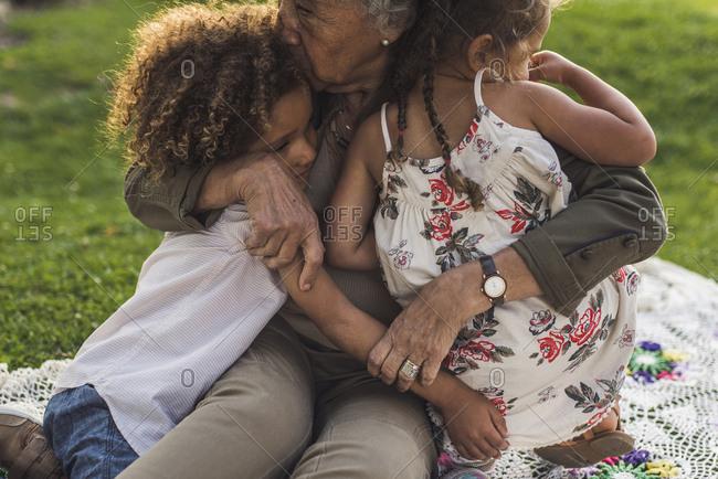 Grandmother embracing grandchildren on picnic blanket at park