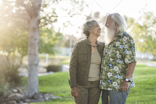 Senior couple looking each other face to face while standing at park