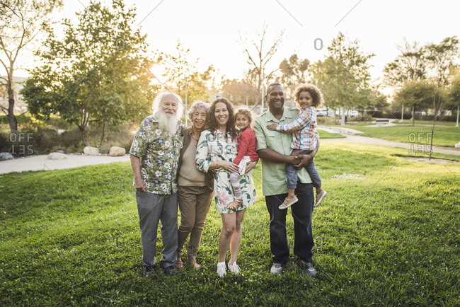 Portrait of happy multi-generation family standing on grassy field at park