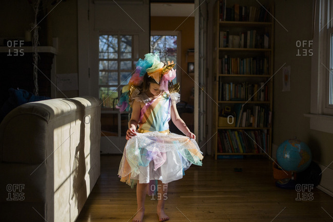 Full length of girl wearing colorful unicorn costume standing on hardwood floor at home