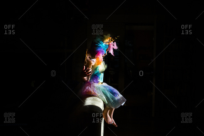 Side view of girl wearing colorful unicorn costume sitting on sofa in darkroom at home