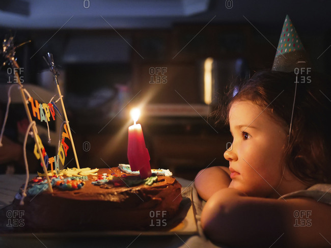 Side view of cute girl looking at birthday cake on table in darkroom