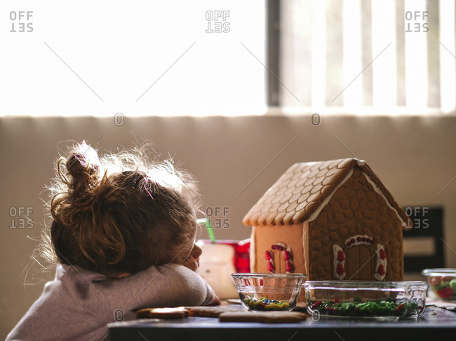 Girl resting by gingerbread house on table at home