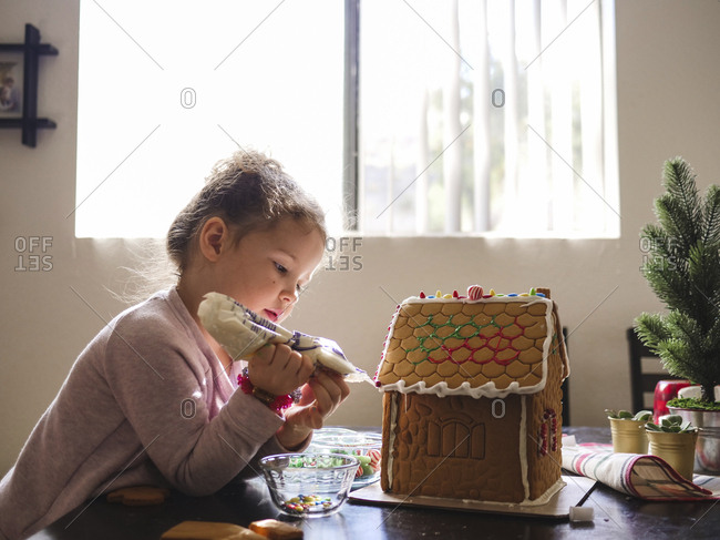 Side view of girl icing gingerbread house on table at home