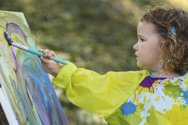 cute baby girl painting on canvas at yard stock photo offset rh offset com