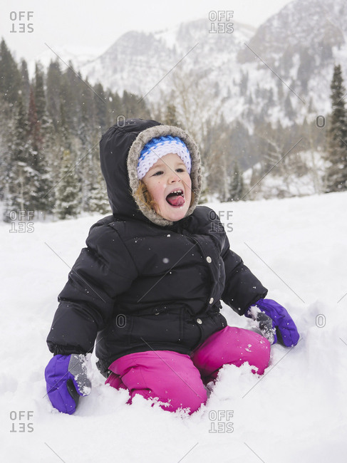 Happy baby girl kneeling on snow covered field against mountain