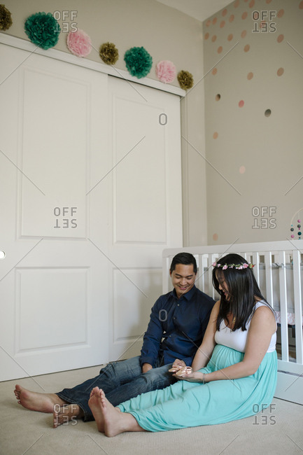 Full length of expectant couple looking at baby booties while sitting against crib
